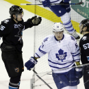 San Jose Sharks' Tommy Wingels (57) celebrates his empty-net goal with teammate Tye McGinn (25) as Toronto Maple Leafs' Jake Gardiner (51) skates past during the third period of an NHL hockey game Thursday, Jan. 15, 2015, in San Jose, Calif. San Jose won