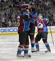 Colorado Avalanche center Nathan MacKinnon (29) jumps on Nate Guenin (5) as Tyson Barrie (4) cheers following Guenin's goal against the Phoenix Coyotes while during the third period of an NHL hockey game on Friday, Feb. 28, 2014, in Denver. (AP Photo/Jack Dempsey)