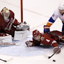 Phoenix Coyotes' Zbynek Michalek (4), of the Czech Republic, pushes the puck away in front of goalie Mike Smith (41) as New York Islanders' Josh Bailey (12) pushes Michalek down and Coyotes' Jordan Szwarz, far right, reaches out for the puck during the th
