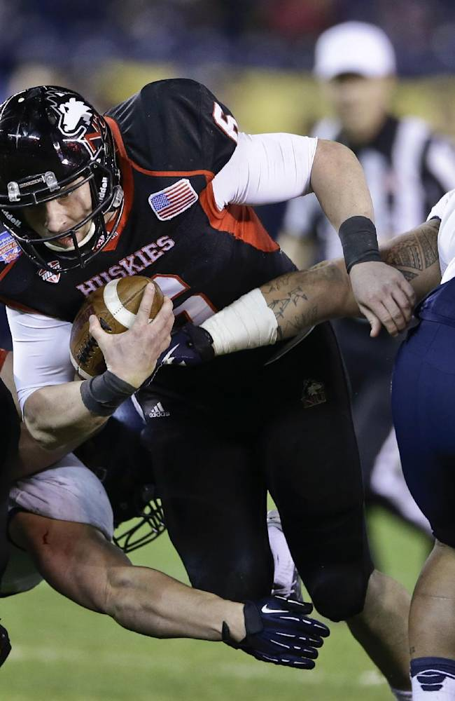 Northern Illinois quarterback Jordan Lynch plows through the Utah State defense for first down during the first half of the Poinsettia Bowl NCAA college football game Thursday, Dec. 26, 2013, in San Diego