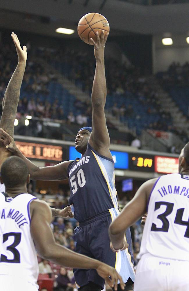 Memphis Grizzlies forward Zach Randolph, center, shoots over Sacramento Kings' Luc Mbah a Moute, of Cameroon, left, and Jason Thompson during the first quarter of an NBA basketball game in Sacramento, Calif., Sunday, Nov. 17, 2013