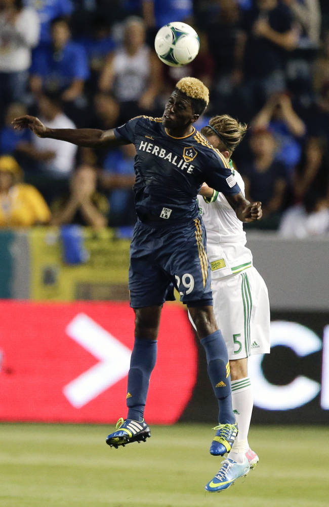 Los Angeles Galaxy forward Gyasi Zardes, left, heads the ball away from Portland Timbers midfielder Michael Harrington during the first half of an MLS soccer match on Wednesday, June 19, 2013 in Carson, Calif