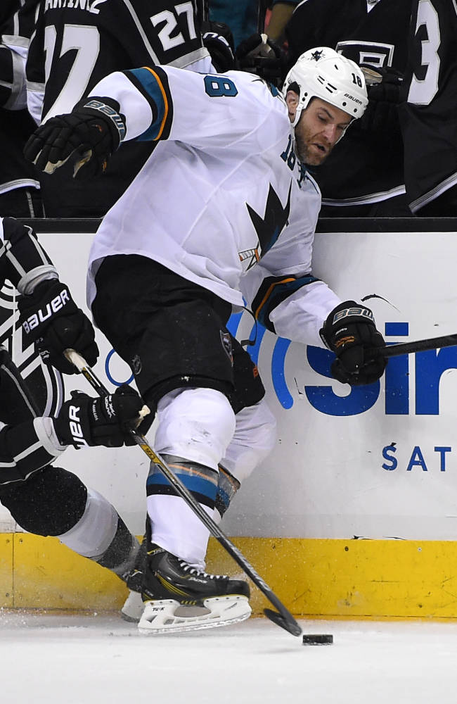 Los Angeles Kings defenseman Slava Voynov, of Russia, left, tangle with San Jose Sharks right wing Mike Brown as he passes the puck during the third period in Game 3 of an NHL hockey first-round playoff series, Tuesday, April 22, 2014, in Los Angeles