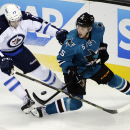 San Jose Sharks defenseman Jason Demers (5) battles against Winnipeg Jets left wing Adam Lowry during the second period of an NHL hockey game Saturday, Oct. 11, 2014, in San Jose, Calif The Associated Press