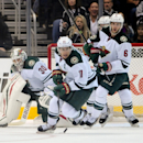 Minnesota Wild left wing Zach Parise (11) and defenseman Marco Scandella (6) help goalie Ilya Bryzgalov (30), of Russia, as a shot is taken during the first period of an NHL hockey game against the Los Angeles Kings, Monday, March 31, 2014, in Los Angeles