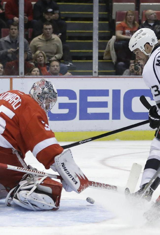 Detroit Red Wings goalie Jimmy Howard (35) deflects a shot by Los Angeles Kings defenseman Willie Mitchell (33) during the first period of an NHL hockey game in Detroit, Saturday, Jan. 18, 2014