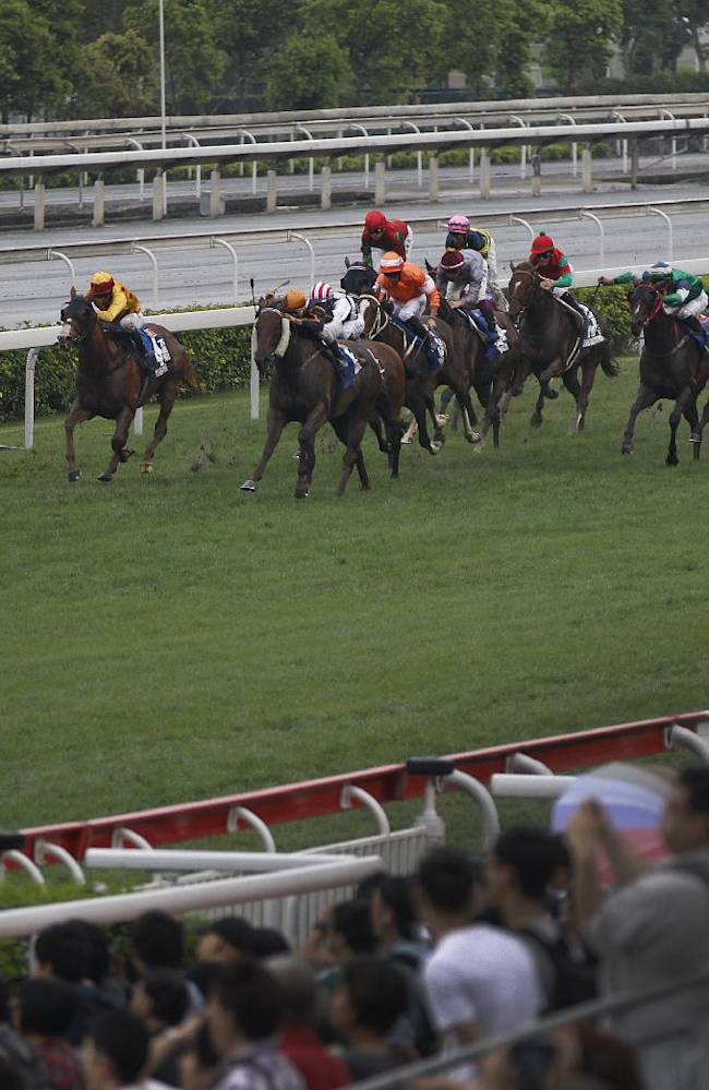 Variety Club from South Africa, left, ridden by Anton Marcus is on the way to win the Champions Mile horse race at the Shatin race track in Hong Kong Sunday, May 4, 2014