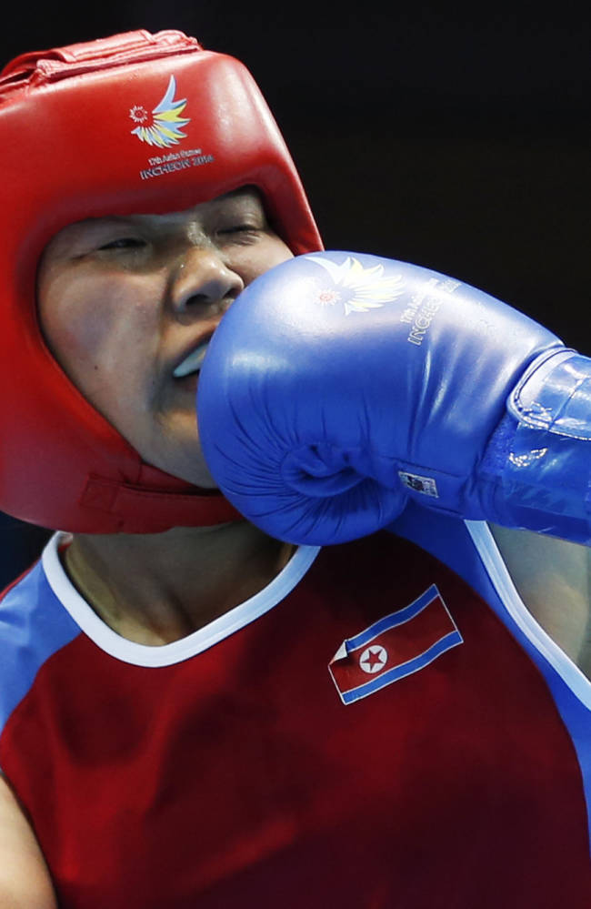 North Korea's Jang Un-hui receives a punch from China's Li Qian during the women's middle (69-75kg) final boxing match at the 17th Asian Games in Incheon, South Korea, Wednesday, Oct. 1, 2014