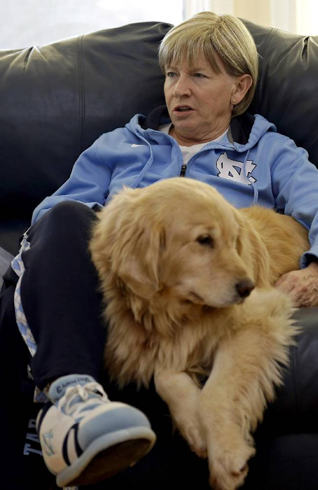 In this Wednesday, Dec. 18, 2013, photo, North Carolina women's basketball coach Sylvia Hatchell relaxes at home with her dog Maddie in Chapel Hill, N.C. After being diagnosed with leukemia, Hatchell has temporarily stepped away from her coaching duties to focus on her treatment