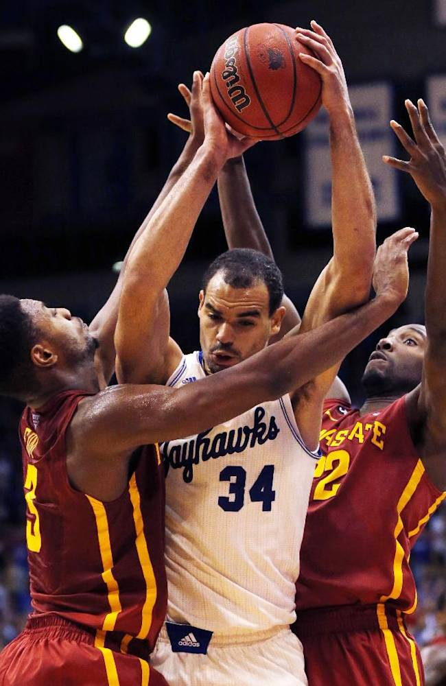 Kansas forward Perry Ellis (34) is fouled by Iowa State forward Melvin Ejim (3) during the second half of an NCAA college basketball game in Lawrence, Kan., Wednesday, Jan. 29, 2014. Iowa State forward Dustin Hogue (22) helps out on the play. Kansas won 92-81