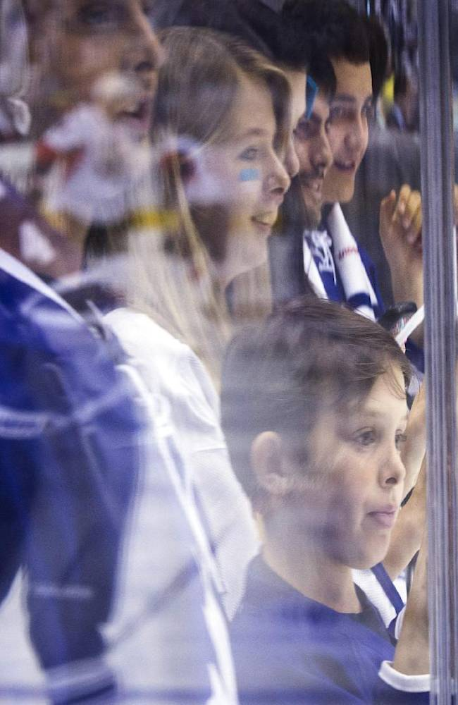 A young boy watches the Toronto Maple Leafs warm up before they play the Ottawa Senators in an NHL hockey game in Toronto, Saturday, Oct. 5, 2013. (AP photo/The Canadian Press, Mark Blinch)