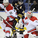 Carolina Hurricanes defenseman Ron Hainsey (65), eyes a rebound with Buffalo Sabres forward Matt Moulson (26) as Hurricanes goaltender Anton Khudobin (31), of Kazakhstan, defendsduring the first period of an NHL hockey preseason game, Tuesday, Sept. 23, 2