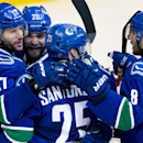 Vancouver Canucks' Ryan Kesler, from left to right, Chris Higgins, Mike Santorelli and Chris Tanev celebrate Kesler's goal against the Colorado Avalanche during third period of an NHL hockey game in Vancouver, British Columbia, on Sunday, Dec. 8, 2013 The