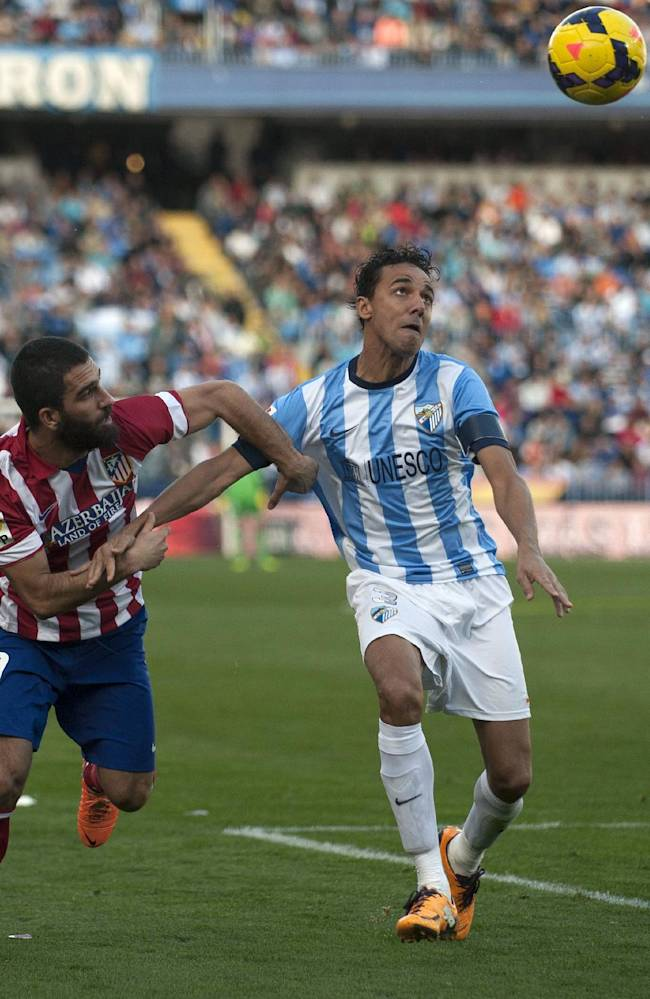 Atletico de Madrid's Arda Turan from Turkey, left, challenges for the ball with Malaga's Welligton from Brazil, right, during a Spanish La Liga soccer match between Malaga and Atletico de Madrid at the La Rosaleda stadium in Malaga, Spain, Saturday, Jan. 4, 2014