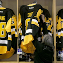 Paula Kos, a sales associate at the Pittsburgh Penguins team store in the Consol Energy Center, adjusts a rack of Sidney Crosby sweaters during the first day of NHL hockey training camp, Friday, Sept. 19, 2014, in Pittsburgh. This new third sweater uses t
