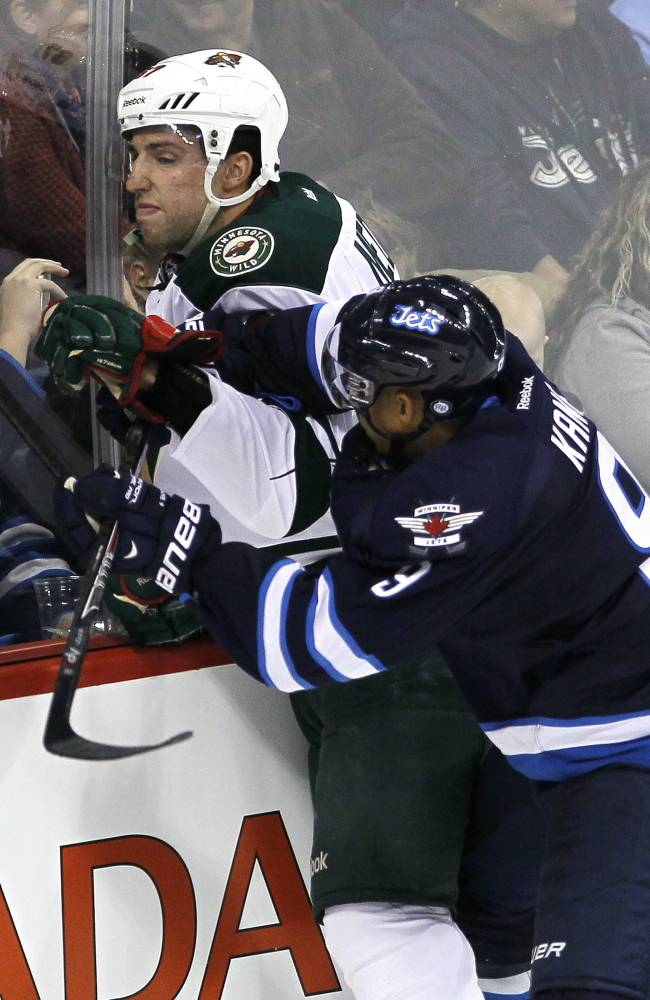 Winnipeg Jets' Evander Kane (9) takes out Minnesota Wild's Kyle Medvec (67) during third-period preseason NHL hockey game action in Winnipeg, Manitoba, Thursday, Sept. 19, 2013