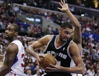 San Antonio Spurs' Tim Duncan, right, gets a rebound against Los Angeles Clippers' Antawn Jamison, left, and Willie Green during the first half of an NBA basketball game on Monday, Dec. 16, 2013, in Los Angeles. (AP Photo/Jae C. Hong)
