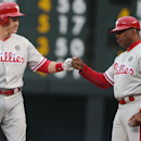 Philadelphia Phillies' Chase Utley, left, is congratulated after hitting a single against the Colorado Rockies by first base coach Juan Samuel in the first inning of a baseball game in Denver on Saturday, April 19, 2014 The Associated Press