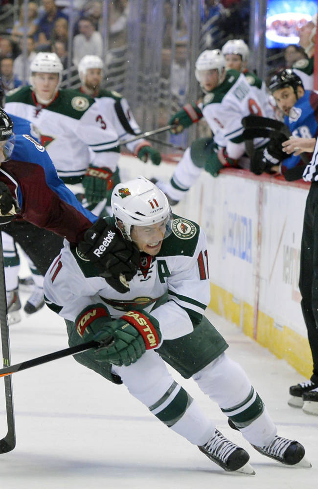 Colorado Avalanche defenseman Jan Hejda (8), from the Czech Republic, hits Minnesota Wild left wing Zach Parise (11) in the chin during the first period in Game 1 of an NHL hockey first-round playoff series on Thursday, April 17, 2014, in Denver
