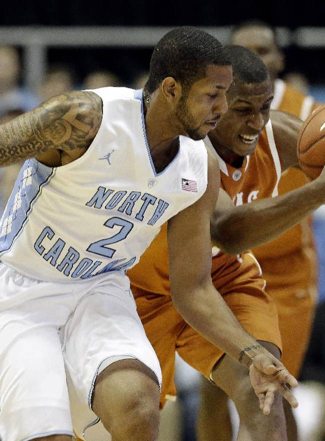 North Carolina's Leslie McDonald (2) and Texas' Jonathan Holmes chase the ball during the first half of an NCAA college basketball game in Chapel Hill, N.C., Wednesday, Dec. 18, 2013