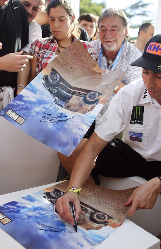 Spains's Joan 'Nani' Roma signs autographs for fans after a news conference in Rosario, Argentina,Thursday, Jan. 2, 2014. The Dakar Rally sets off on Jan. 5, from Rosario in Argentina, crosses through Bolivia's high-altitude salt flats and finishes in Valparaiso, Chile, on Jan. 18