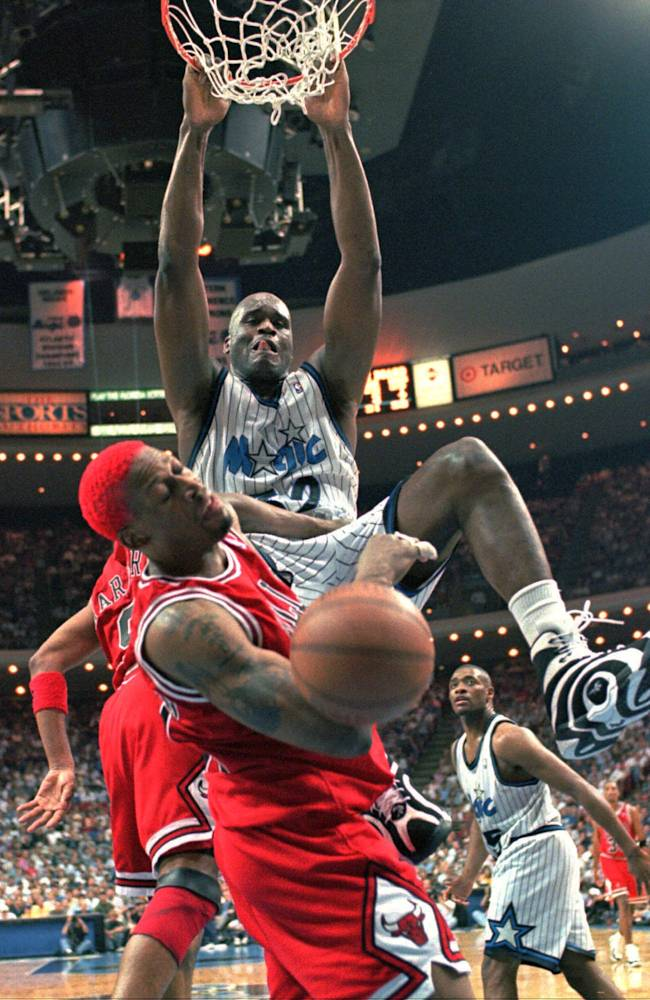 FILE - This April 7, 1996, file photo shows Orlando Magic's Shaquille O'Neal  dunking the ball and knocking Chicago Bulls' Dennis Rodman out of the way at the same time during their game in Orlando. The Orlando Magic are inducting Shaquille O'Neal into the team's Hall of Fame. The Magic announced O'Neal's addition Thursday, March 12, 2015. He will be honored on March 27, when the Magic host the Detroit Pistons.  (AP Photo/Steve Simoneau, File)
