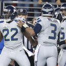 Seattle Seahawks running back Robert Turbin (22) celebrates after scoring on a 13-yard touchdown reception from quarterback Russell Wilson (3) against the San Francisco 49ers during the first quarter of an NFL football game in Santa Clara, Calif., Thursday, Nov. 27, 2014. (AP Photo/Tony Avelar)