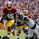 Washington Redskins running back Alfred Morris (46) jumps away from Jacksonville Jaguars linebacker Dekoda Watson to score a touchdown in during the first half of an NFL football game Sunday, Sept. 14, 2014, in Landover, Md The Associated Press
