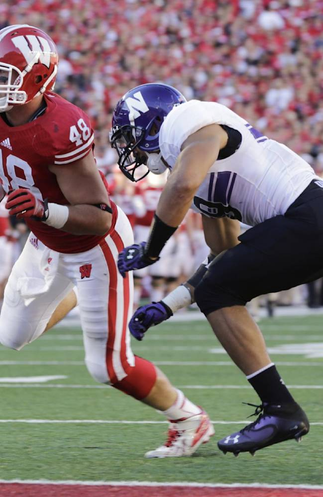 Wisconsin tight end Jacob Pedersen (48) runs in for a 1-yard touchdown against Northwestern safety Jimmy Hall during the second half of an NCAA college football game in Madison, Wis., Saturday, Oct. 12, 2013. Wisconsin upset Northwestern 35-6