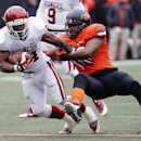 Oklahoma running back Brennan Clay, left, is tackled by Oklahoma State linebacker Ryan Simmons in the second quarter of an NCAA college football game in Stillwater, Okla., Saturday, Dec. 7, 2013. Oklahoma won 33-24 The Associated Press