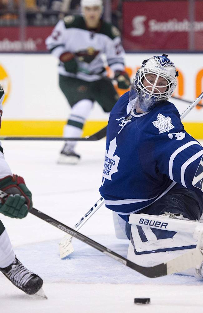 Toronto Maple Leafs goaltender James Reimer, right, makes a save on Minnesota Wild forward Mikael Granlund during the third period of an NHL hockey game in Toronto on Tuesday, Oct. 15, 2013. Toronto won 4-1