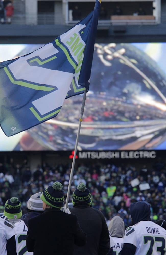 The Vince Lombardi Trophy is displayed on the big screen behind the Seattle Seahawks and a