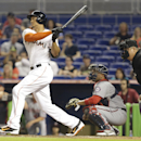 Miami Marlins right fielder Giancarlo Stanton, left, follows through on a double as Washington Nationals catcher Sandy Leon, right, looks on during the first inning of the MLB National League baseball game, Monday, April 14, 2014, in Miami The Associated