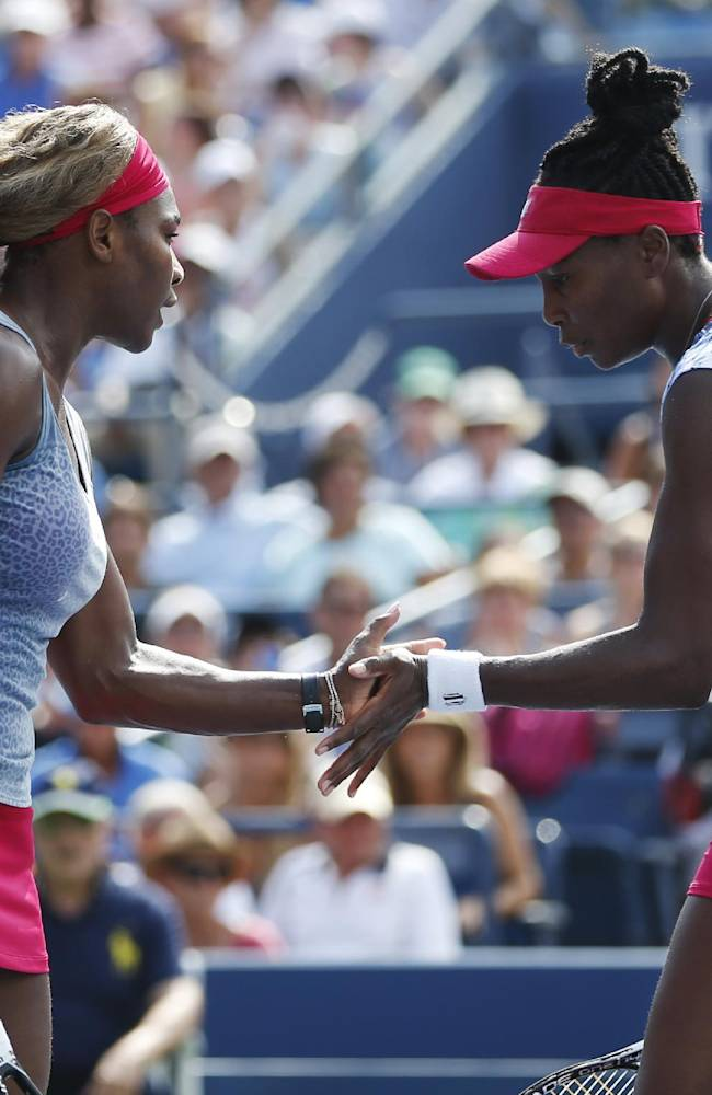 Serena, left, and Venus Williams slap hands between points against Garbine Muguruza and Carla Suarez Navarro, of Spain, during a doubles match at the 2014 U.S. Open tennis tournament, Sunday, Aug. 31, 2014, in New York