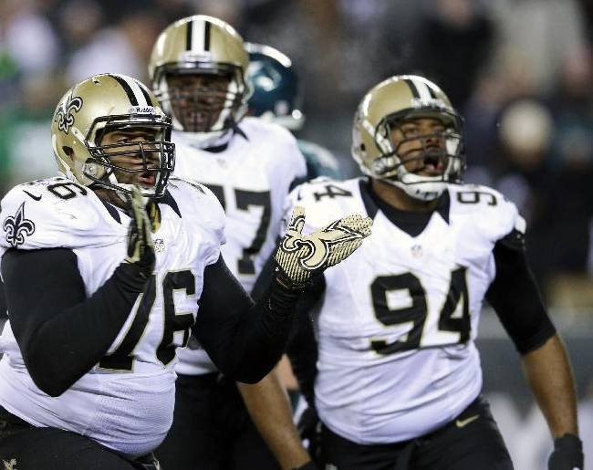 New Orleans Saints' Akiem Hicks (76) and Cameron Jordan (94) celebrate after tackling Philadelphia Eagles' Nick Foles during the second half of an NFL wild-card playoff football game, Saturday, Jan. 4, 2014, in Philadelphia