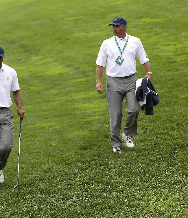 United States team player Tiger Woods, left, and team captain Fred Couples walk to the 17th green during the single matches at the Presidents Cup golf tournament at Muirfield Village Golf Club Sunday, Oct. 6, 2013, in Dublin, Ohio