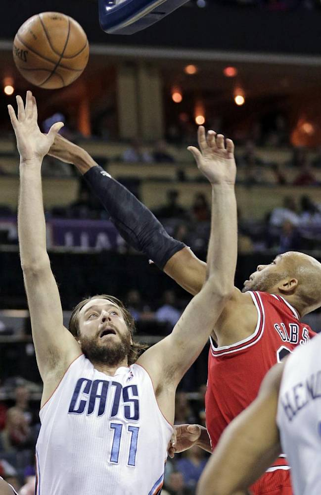 Charlotte Bobcats' Josh McRoberts, left, has his shot blocked by Chicago Bulls' Taj Gibson, right, during the first half of an NBA basketball game in Charlotte, N.C., Saturday, Jan. 25, 2014