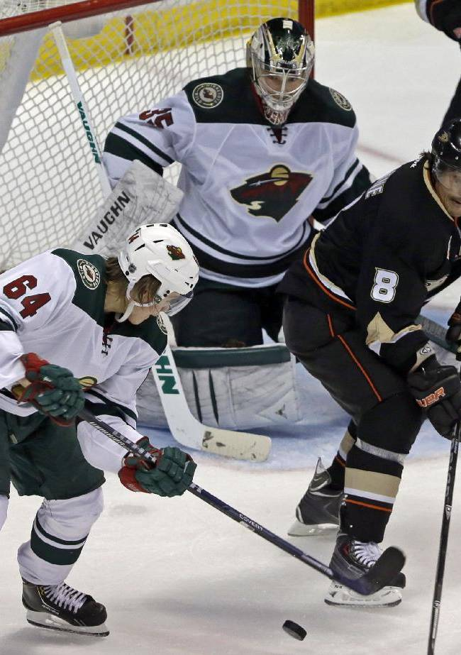 Anaheim Ducks right winger Teemu Selanne (8), of Finland, maneuvers the puck with Minnesota Wild center Mikael Granlund (64), of Finland, and goalie Darcy Kuemper (35) defending in the second period of an NHL hockey game in Anaheim, Calif., Tuesday, Jan. 28, 2014