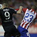 Chelsea's Fernando Torres, left heads the ball under pressure form Atletico's Miranda during the Champions League semifinal first leg soccer match between Atletico Madrid and Chelsea at the Vicente Calderon stadium in Madrid, Spain, Tuesday, April 22, 201