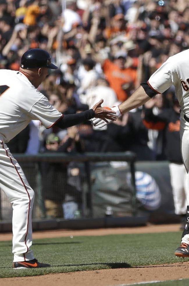 CORRECTS TO THREE-RUN San Francisco Giants' Brandon Hicks, right, celebrates with third base coach Tim Flannery after hitting the game-winning three-run homer off Cleveland Indians' Cody Allen in the ninth inning of a baseball game, Sunday, April 27, 2014, in San Francisco. The Giants won 4-1