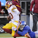 Washington Redskins quarterback Robert Griffin III (10) is tackled by New York Giants defensive end Damontre Moore (98) during the fourth quarter of an NFL football game, Sunday, Dec. 14, 2014, in East Rutherford, N.J The Associated Press