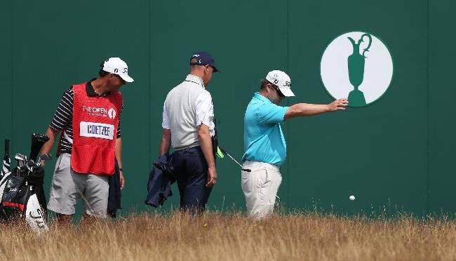 George Coetzee of South Africa is watched by his caddie and a member of the rules committee as he takes a drop shot on the 18th during the second day of the British Open Golf championship at the Royal Liverpool golf club, Hoylake, England, Friday July 18, 2014