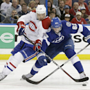 Montreal Canadiens left wing Rene Bourque (17) battles Tampa Bay Lightning defenseman Andrej Sustr (62), of the Czech Republic, for the puck during the third period of Game 2 of a first-round NHL hockey playoff series on Friday, April 18, 2014, in Tampa,