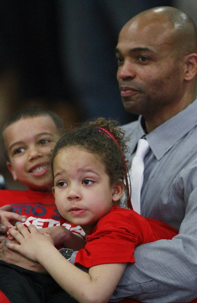 Metro State head coach Derrick Clark, right, plays with his 5-year-old twins, Isaiah, back left, and Alexis, after Metro State's 77-71 victory over Colorado-Colorado Springs in an NCAA college basketball game for the championship of the Rocky Mountain Athletic Conference men's tournament in Denver on Saturday, March 8, 2014