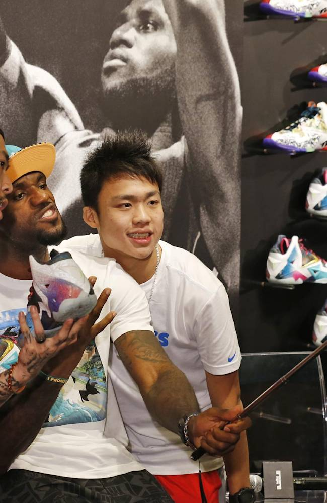 NBA star LeBron James uses his fan's smartphone to take a selfie during a promotional event at a shopping district in Hong Kong as part of his China tour Wednesday, July 23, 2014. Earlier this month, James left the Miami Heat after four seasons and four trips to the NBA Finals and re-signed with the Cavaliers, where his career began. (AP Photo/Kin Cheung)