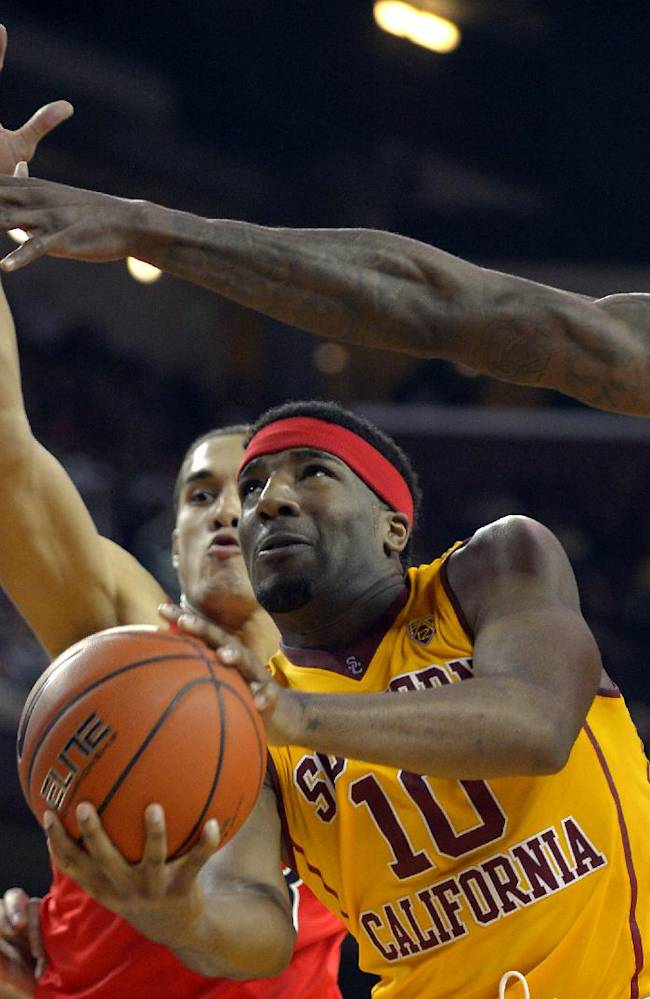 Southern California guard Pe'Shon Howard, center, puts up a shot as Arizona guard Nick Johnson, second from left, and forward Rondae Hollis-Jefferson, right, defend during the second half of an NCAA college basketball game, Sunday, Jan. 12, 2014, in Los Angeles