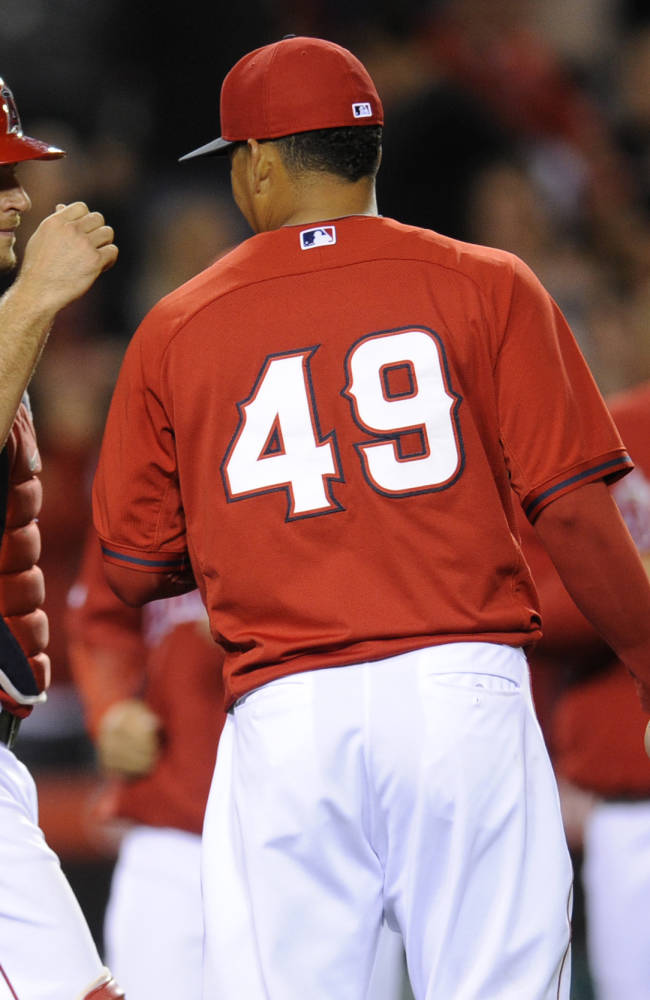 Los Angeles Angels relief pitcher Ernesto Frieri, center, celebrates with Los Angeles Angels catcher Chris Iannetta, left, after defeating the Los Angeles Dodgers 6-2 in a spring exhibition baseball game in Anaheim, Calif., Saturday, March 29, 2014