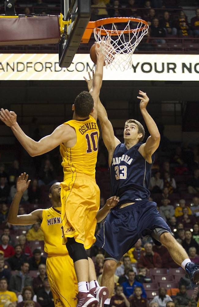 Concordia-St. Paul forward Chris Halvorsen (33) has his shot blocked by Minnesota forward Oto Osenieks (10) during the first half of an NCAA college exhibition basketball game, Monday, Nov. 4, 2013, in Minneapolis