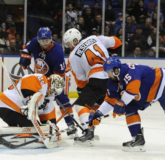 Philadelphia Flyers goalie Ray Emery (29) and Andrej Meszaros (41) defend against New York Islanders' Josh Bailey (12) and Cal Clutterbuck (15) in the second period of an NHL hockey game on Monday, Jan. 20, 2014, in Uniondale, N.Y