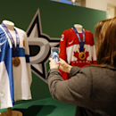 Dallas Stars fans take photos of medals won at the recent Winter Olympics by Stars goalie Kari Lehtonen, of Finland and center Jamie Benn before an NHL hockey game against the Carolina Hurricanes, Thursday, Feb. 27, 2014, in Dallas The Associated Press